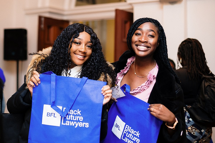 Two black women holding blue Black Future Lawyer bag