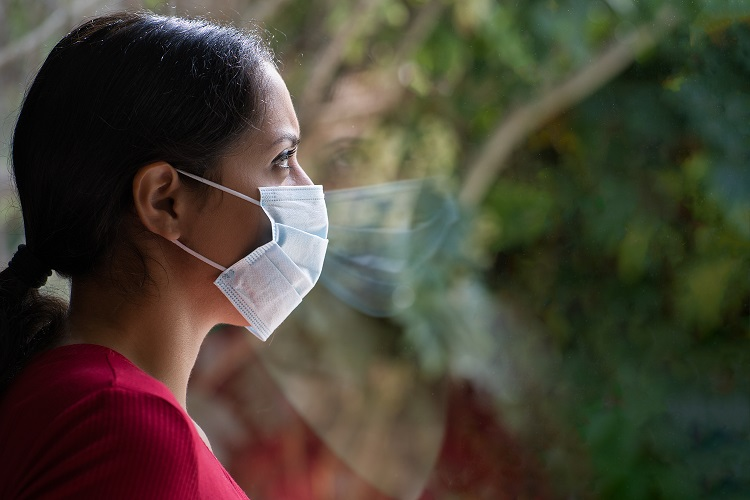 Woman with face mask looking out window