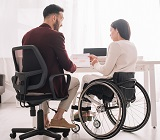 man in chair next to woman in wheelchair
