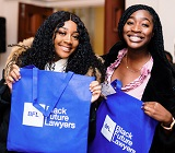 Two black women holding blue Black Future Lawyer bags