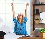 Woman at desk, arms raised in victory