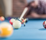 Billiard table,  person lining up a shot