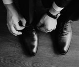 a pair of hands tying a set of dress shoes