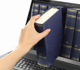 A hand reaching into a laptop monitor and pulling out a book